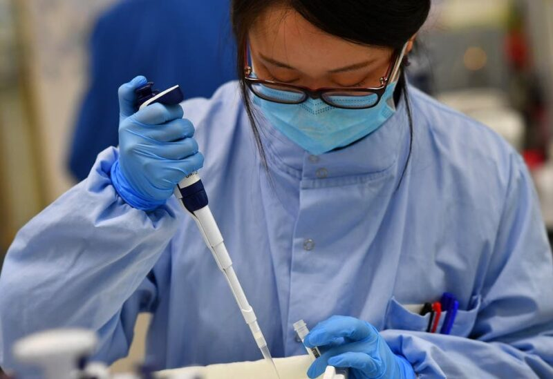 Scientists work at a laboratory where they sequence the novel coronavirus genomes at COVID-19 Genomics UK, on the Wellcome Sanger Institute's 55-acre campus south of Cambridge, Britain March 12, 2021. Picture taken March 12, 2021. (Reuters)