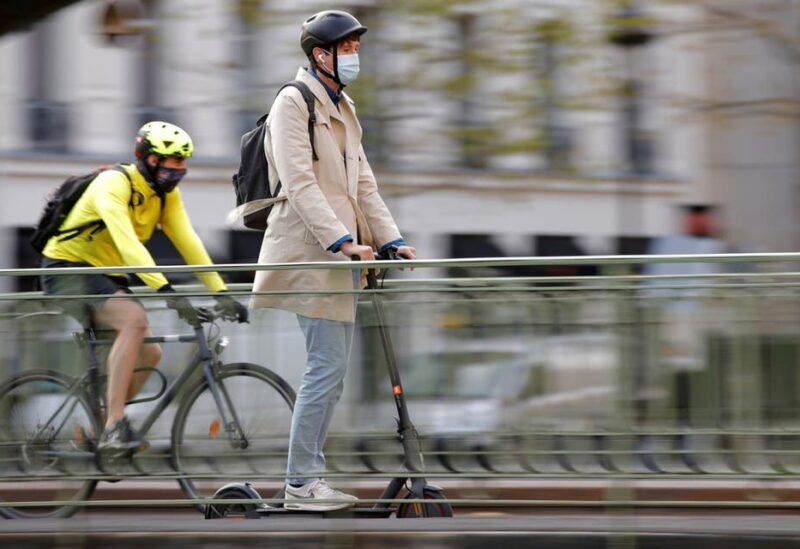 A man, wearing a protective face mask, rides a scooter past a biker on a bridge over the canal Saint-Martin in Paris amid the coronavirus (COVID-19) outbreak in France, April 22, 2021. (File photo: Reuters)
