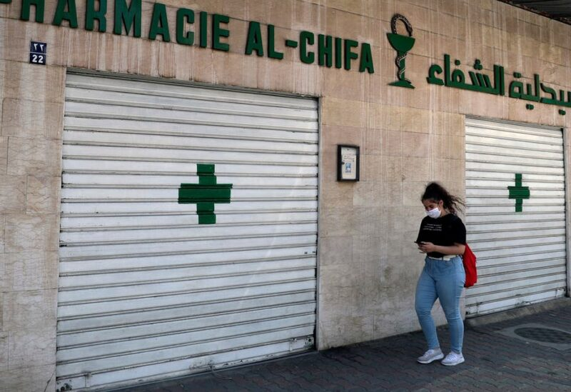 A woman passes by a closed pharmacy in Beirut, Lebanon, Friday, June 11, 2021. (AP)