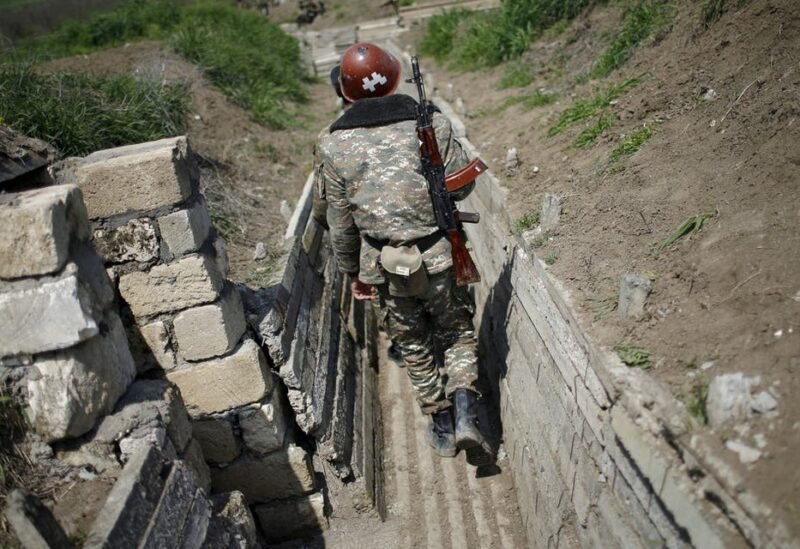 A file photo shows ethnic Armenian soldiers walk in a trench at their position near Nagorno-Karabakh's boundary, April 8, 2016. (Reuters)