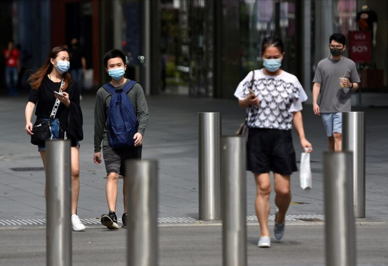 People wearing face masks cross a road amid the coronavirus disease (COVID-19) outbreak in Singapore May 20, 2021. REUTERS/Caroline Chia