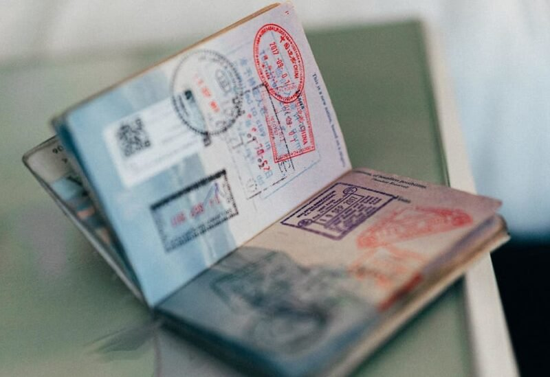 A passport with country entry stamps is pictured. (Unsplash, Henry Thong)