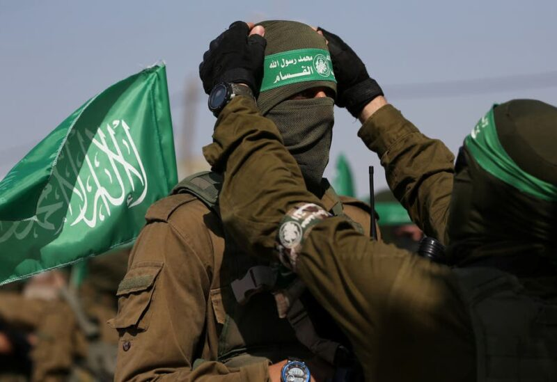 A Palestinian Hamas militant adjusts the mask and headband of his comrade during an anti-Israel military show in the southern Gaza Strip November 11, 2019. (Reuters)