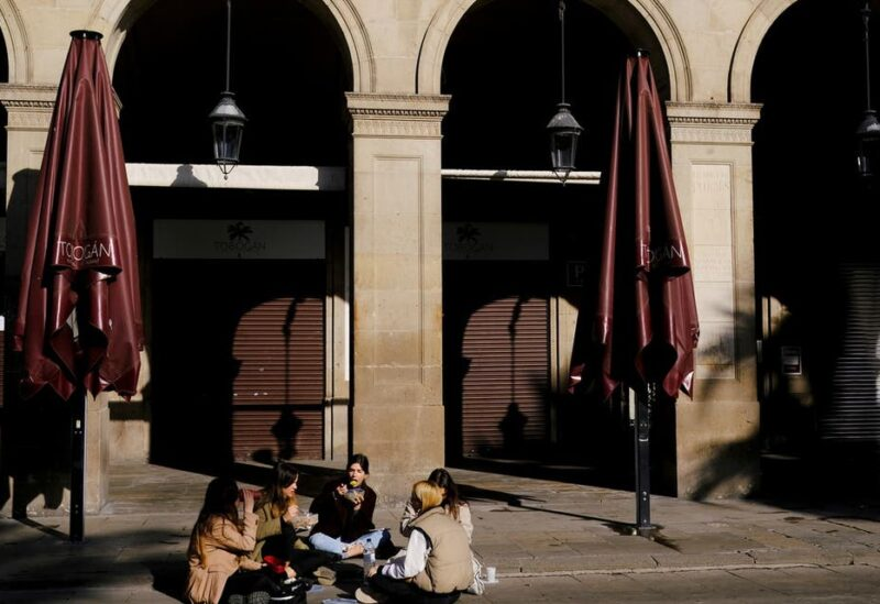 Women eat while sitting in front of a closed restaurant at the empty Plaza Reial (Reial square), after Catalonia's government imposed new restrictions in an effort to control the spread of the coronavirus disease (COVID-19), in Barcelona, Spain January 26, 2021. (Reuters)