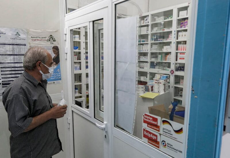 A man, mask-clad due to the COVID-19 coronavirus pandemic, waits to receive medication from the pharmacy of the Amel NGO in Lebanon's southern coastal city of Tyre on July 22, 2020. (File photo: AFP)