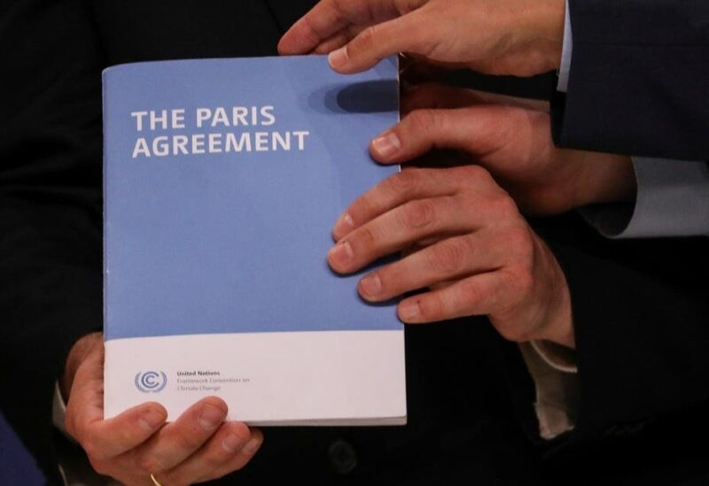 COP25 High Level Climate Champion Gonzalo Munoz holds the copy of The Paris Agreement as he poses with Britain's former Minister of State for Energy and Clean Growth and newly appointed COP26 President, Claire Perry, Italian Environment Minister Sergio Costa and Spanish State Secretary of Environment Hugo Moran (not pictured) during the U.N. Climate Change Conference (COP25) in Madrid, Spain December 13, 2019. (Reuters)