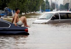 A man sits on a stranded vehicle on a flooded road following heavy rainfall in Zhengzhou, Henan province, China July 22, 2021. (Reuters)