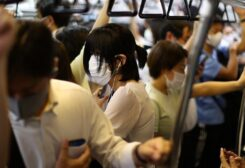 People wearing protective masks amid the coronavirus pandemic take a train on the outskirts of Tokyo, Japan, on August 5, 2021. (Reuters)