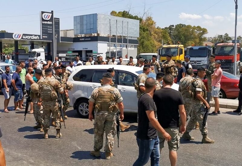 Lebanese army soldiers try to open a road blocked by cars near a gas station in Sidon, Lebanon August 12, 2021. (Reuters)