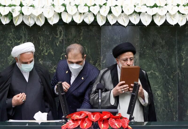Iran's new President Ebrahim Raisi kisses the Quran during his swearing-in ceremony at the parliament in Tehran, Iran, August 5, 2021. (Reuters)