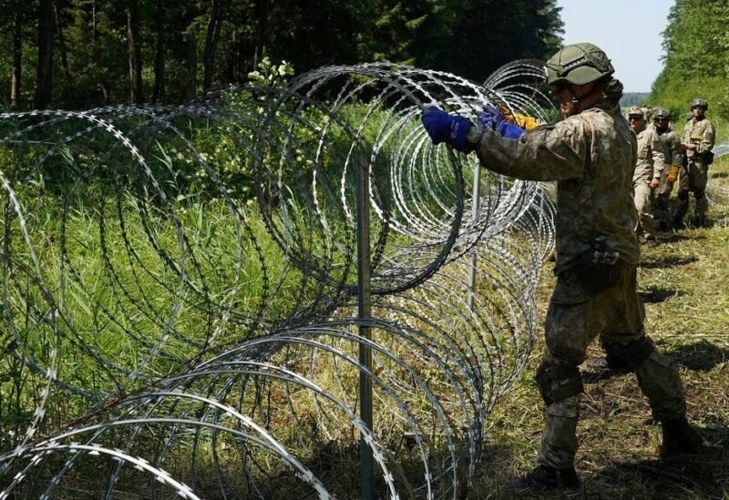 Lithuanian army soldiers install razor wire on border with Belarus in Druskininkai, Lithuania, on July 9, 2021. (Reuters)