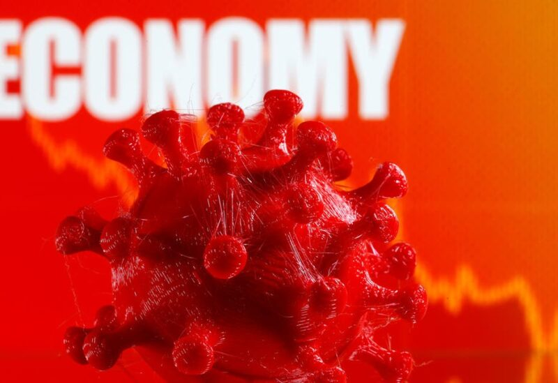 A 3D-printed coronavirus model is seen in front of a stock graph and the word Economy on display in this illustration taken March 25, 2020. (Reuters)
