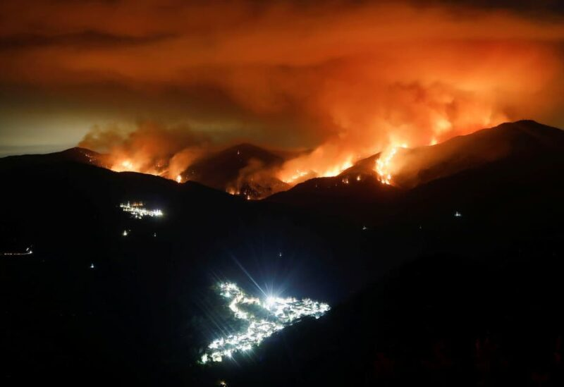 A wildfire is seen at night on Sierra Bermeja Mountain, near the towns of Genalguacil (L) and Benarraba (bottom), southern Spain, September 10, 2021. Picture taken with a long exposure. (Reuters)