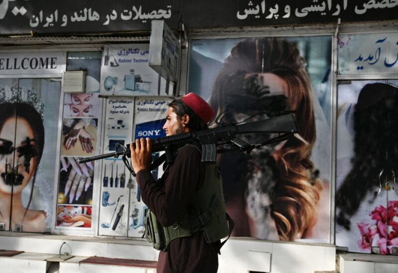A Taliban fighter walks past a beauty salon with images of women defaced using spray paint in Shar-e-Naw in Kabul on August 18, 2021. (AFP)