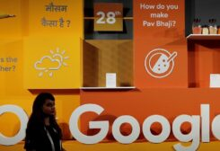 A woman walks past the logo of Google during an event in New Delhi, India. (Reuters)