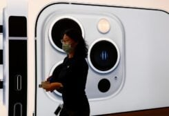 An Apple employee wearing a face mask walks past an image of an iPhone 13 Pro at an Apple Store on the day the new Apple iPhone 13 series goes on sale, in Beijing, China, September 24, 2021. (Reuters)