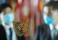 People wearing face masks are seen behind the emblem of the United Nations at its headquarters. (Reuters)