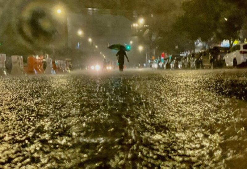 A person makes their way in rainfall from the remnants of Hurricane Ida on September 1, 2021, in the Bronx borough of New York City. The once category 4 hurricane passed through New York City, dumping 3.15 inches of rain in the span of an hour at Central Park. (AFP)